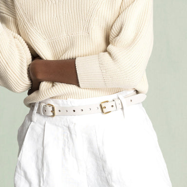 closeup of white belt on whit shorts green background
