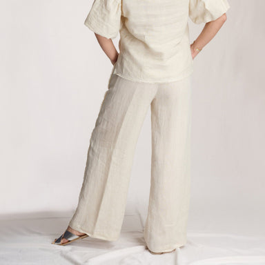 rear view woman wearing linen pants in front of white background