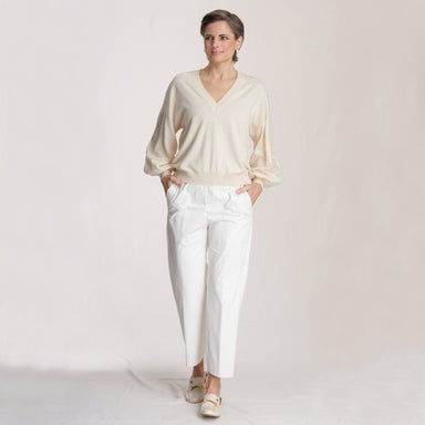 fully body view woman wearing beige top and white pants in front of white background