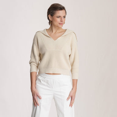 woman wearing beige polo sweater with white pants in front of white background