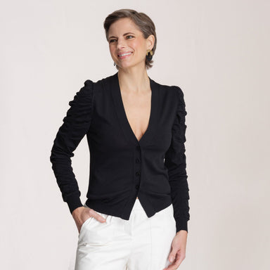 woman wearing black sweater with white pants in front of white background