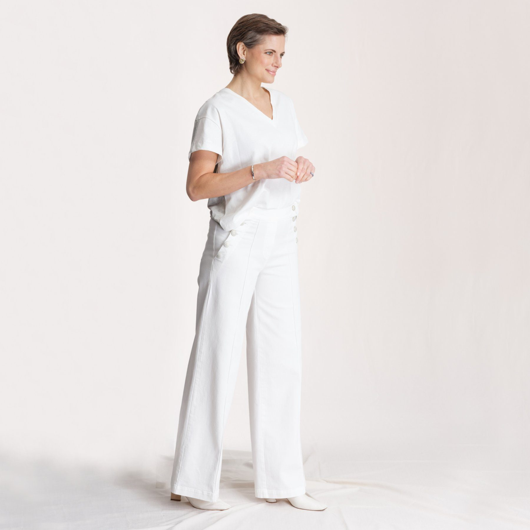 woman wearing white t shirt and white sailor pants in front of white background