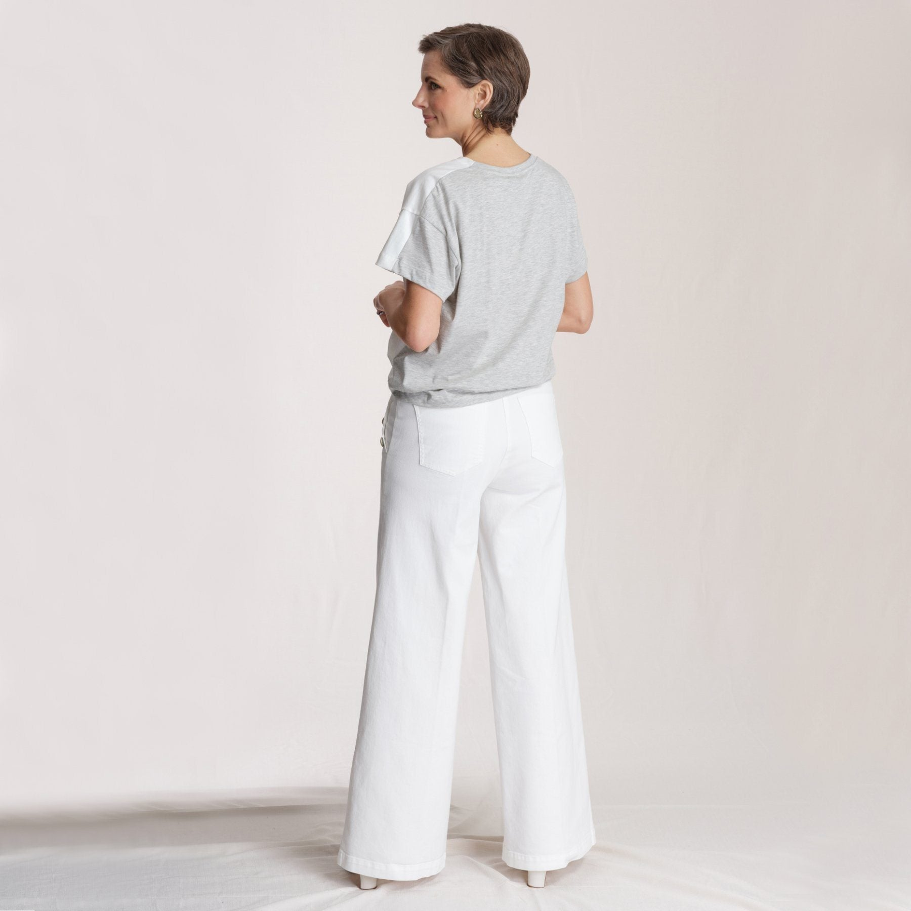 rear view woman wearing grey t shirt and white pants in front of white background