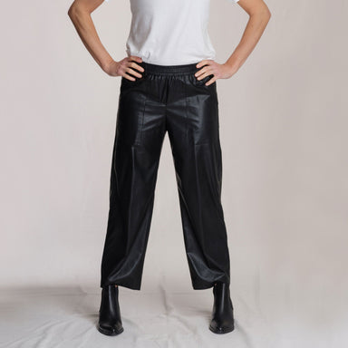 woman wearing black leather pants in front of white background