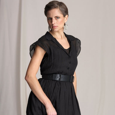 woman wearing black dress with belt in front of grey background