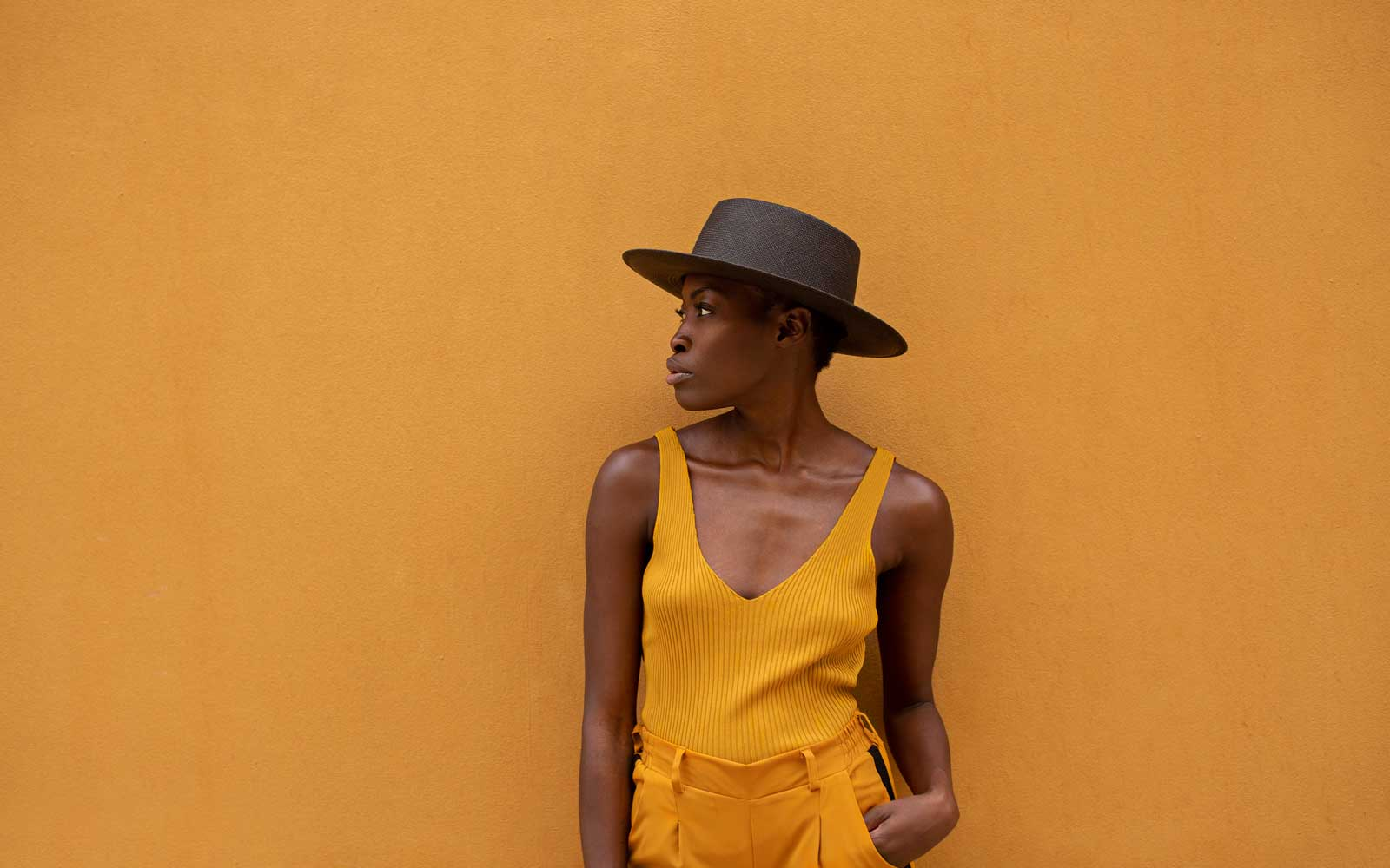 woman wearing black flat woven hat in front of yellow wall