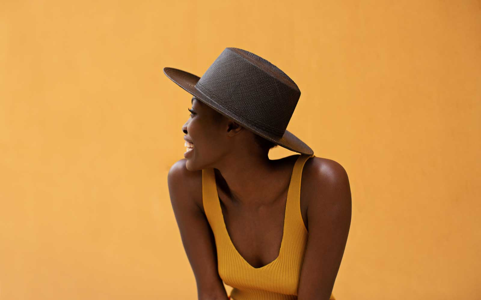 woman wearing black woven hat in front of yellow wall