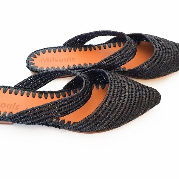 Side close view photo of black pointed toe slip on flats made from raffia grass and leather