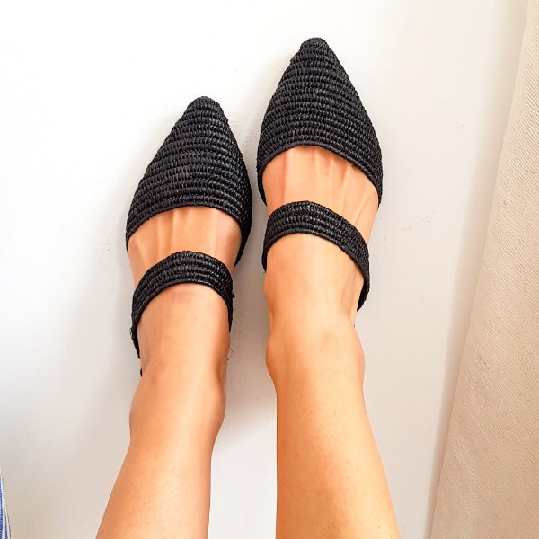 Top view of feet in black pointed toe slip on flats made from raffia grass and leather