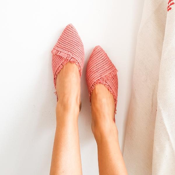 Top view of model wearing pink pointed toe slip on mules made from raffia grass and leather