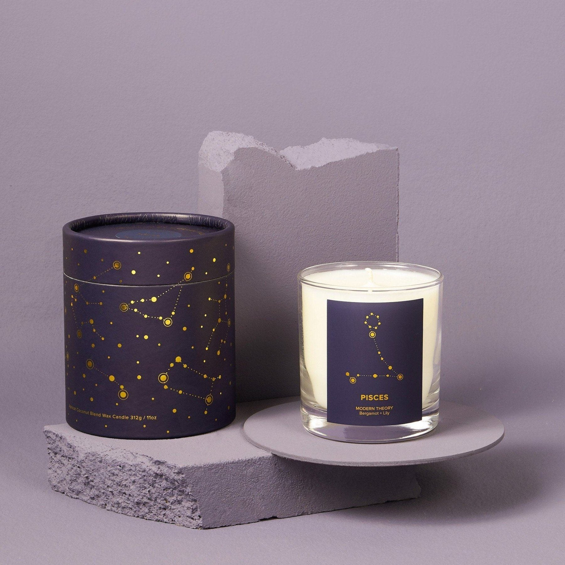 white candle in glass jar with pisces label next to matching navy decorative box with astrology pattern