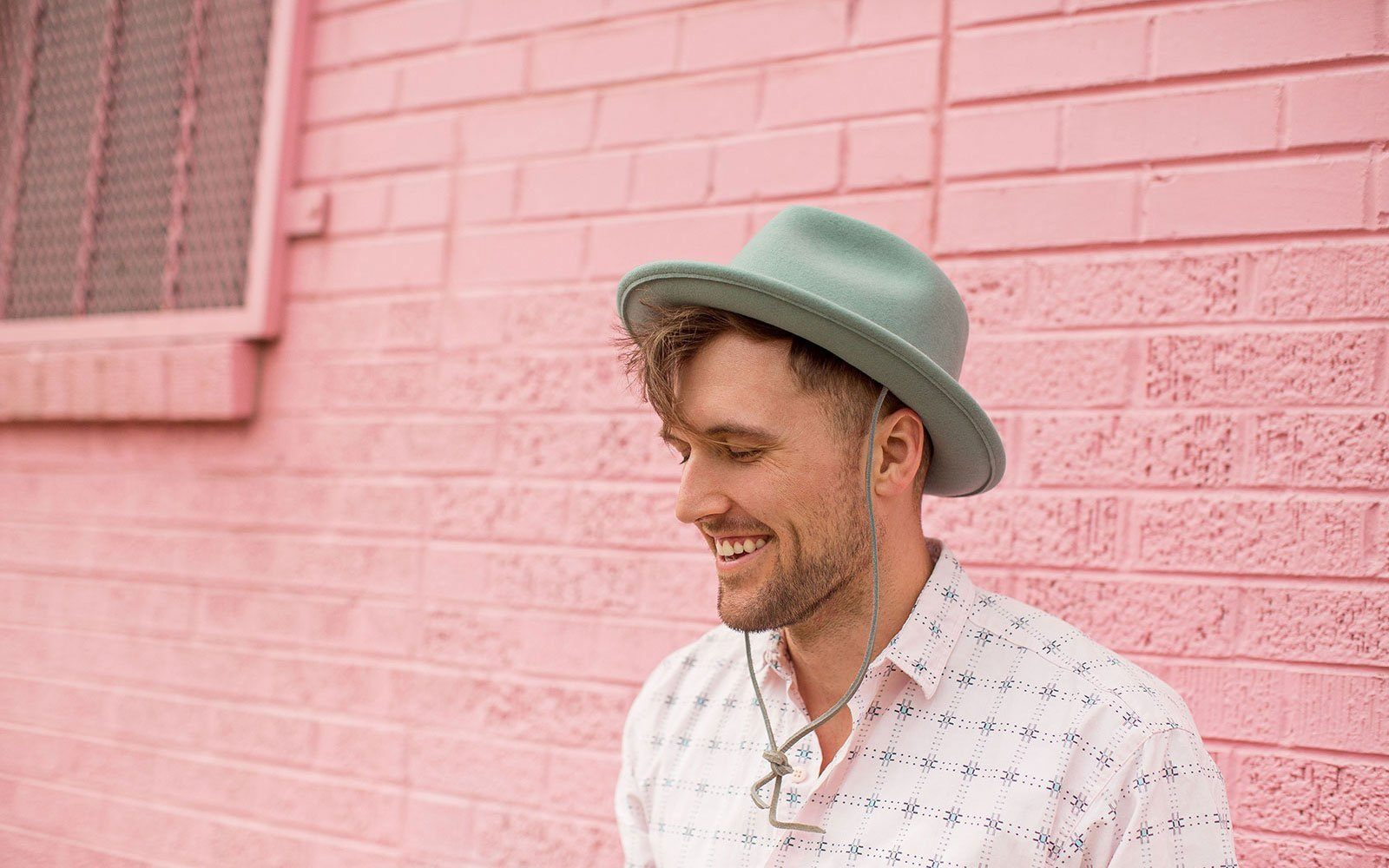 man wearing light green wool felt hat in front of red wall