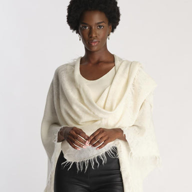 model posing with black leather pants, white top and ivory knit shawl with fringe detail on edges