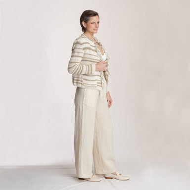 side view woman wearing striped jacket and linen pants in front of white background