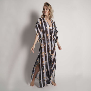 model against white background wearing sheer long kimono coverup with black and white stripes and yellow floral pattern