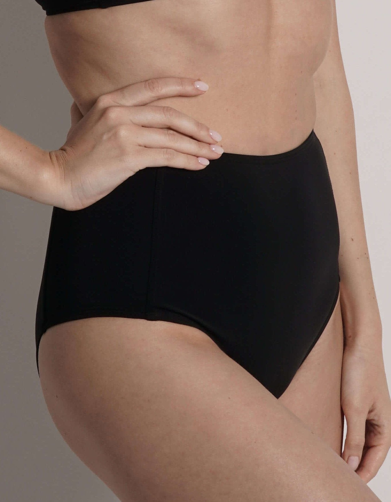 close up of model wearing high waist swim bottom in black