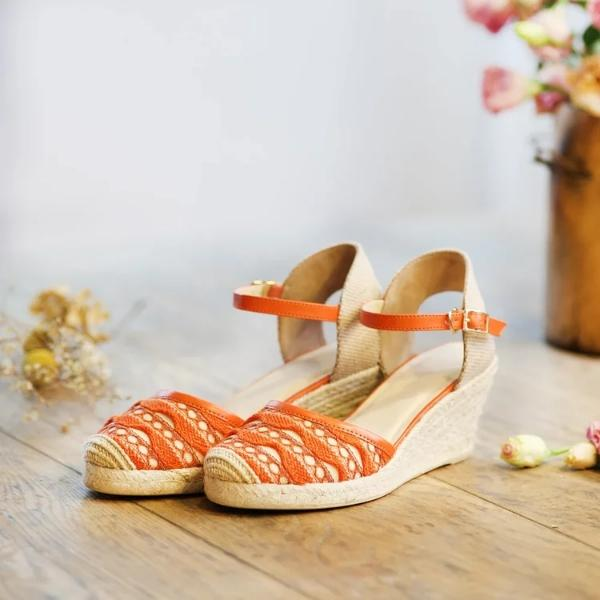 Side view of knit wedge sandal with closed toe and orange woven pattern