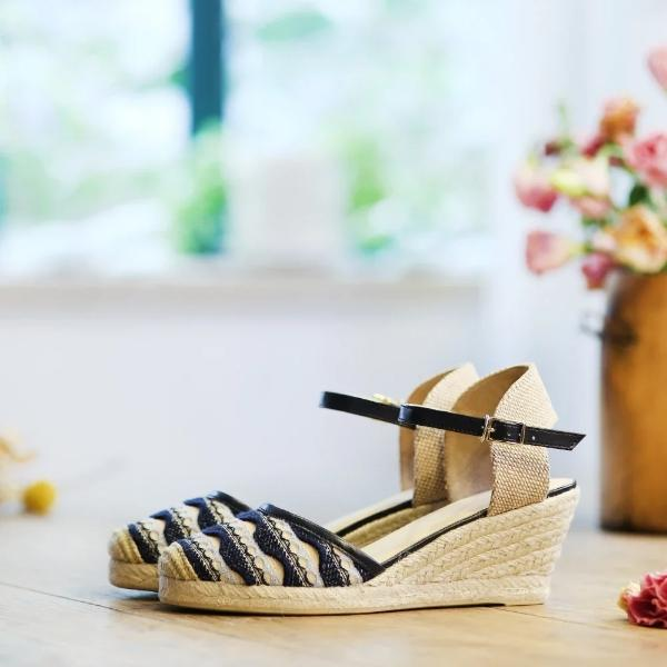 Photo of knit wedge sandal with buckle close toe and black woven pattern