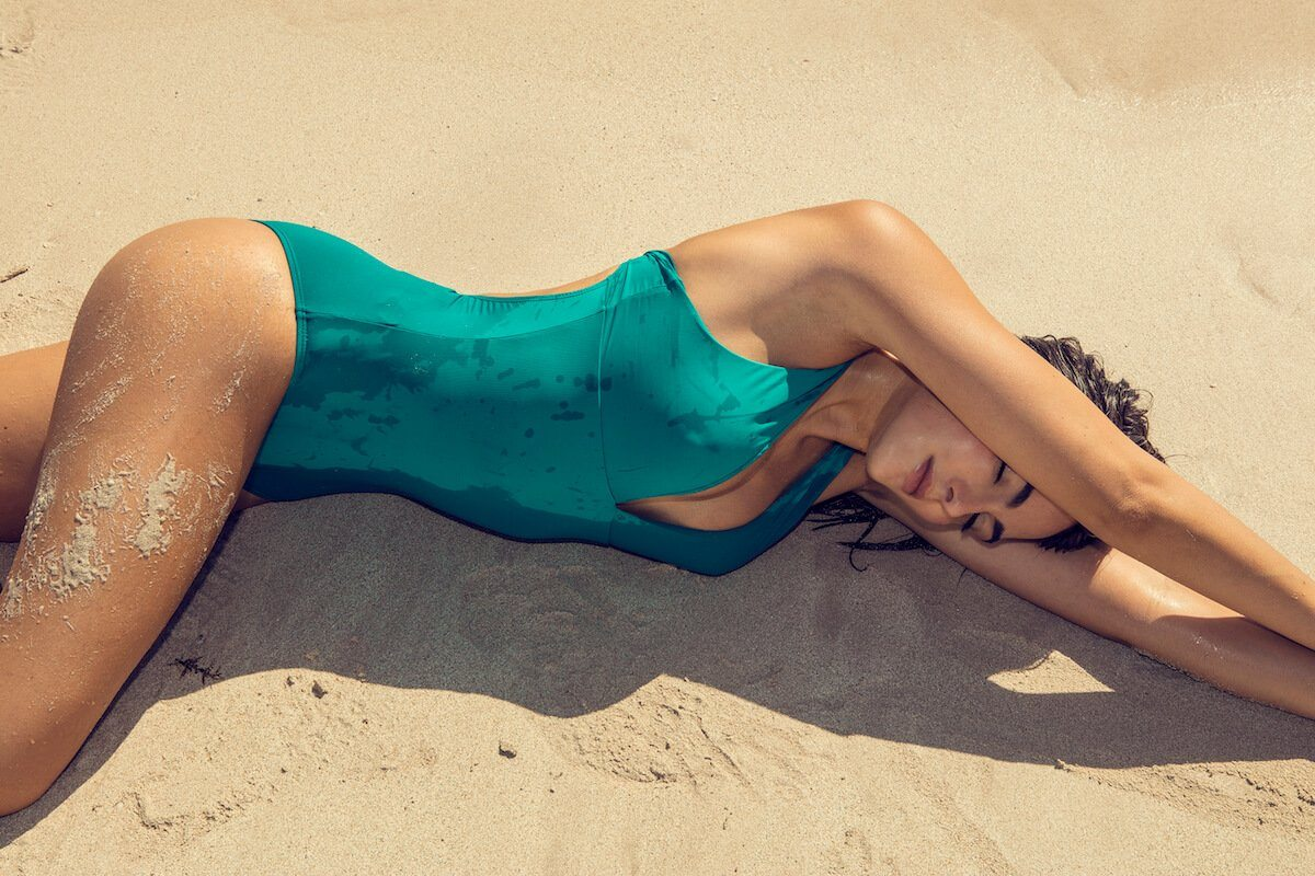 model on beach laying in sand in green one piece