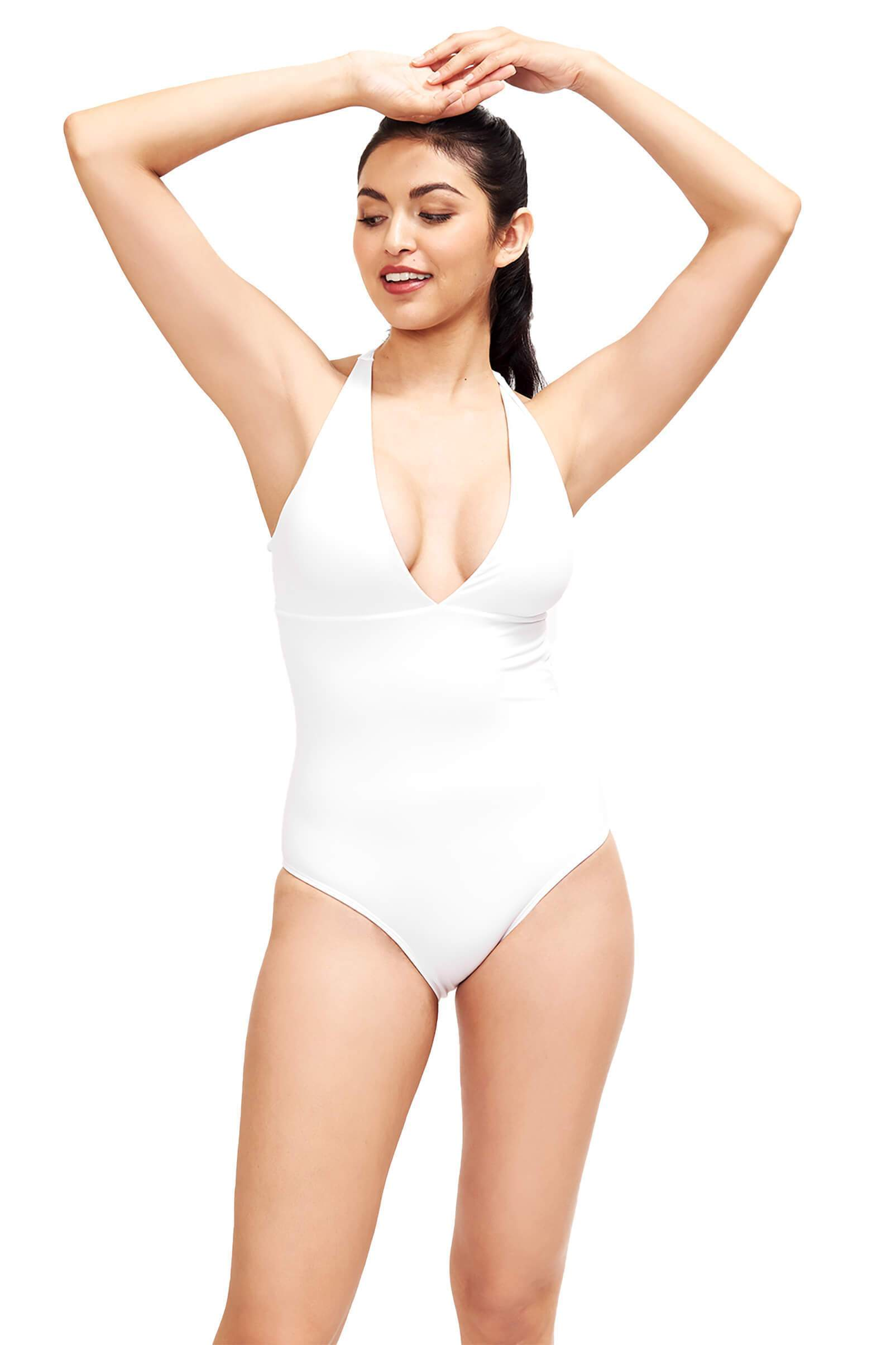 model with hands in air wearing white deep v neck one piece