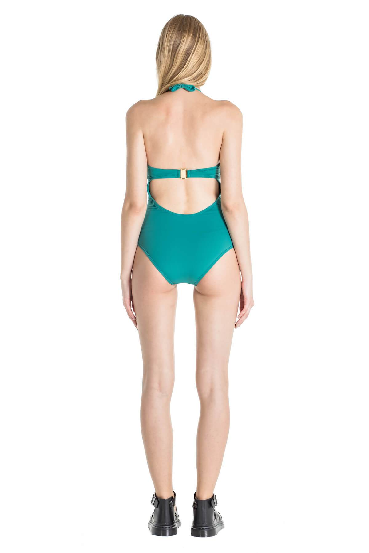 back of model wearing green one piece with halter tie at neck and one strap across back