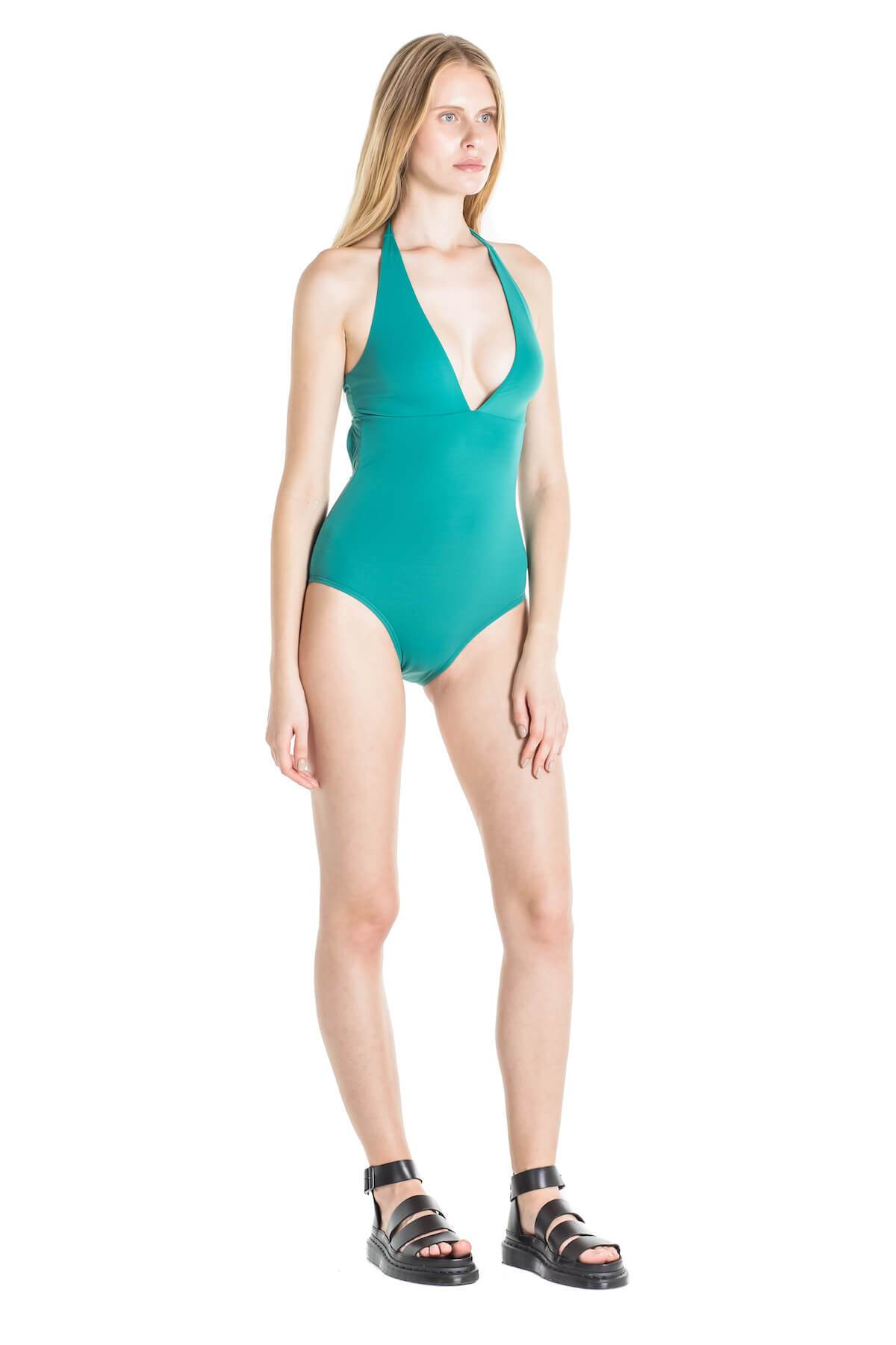side of model wearing green one piece with plunging neckline