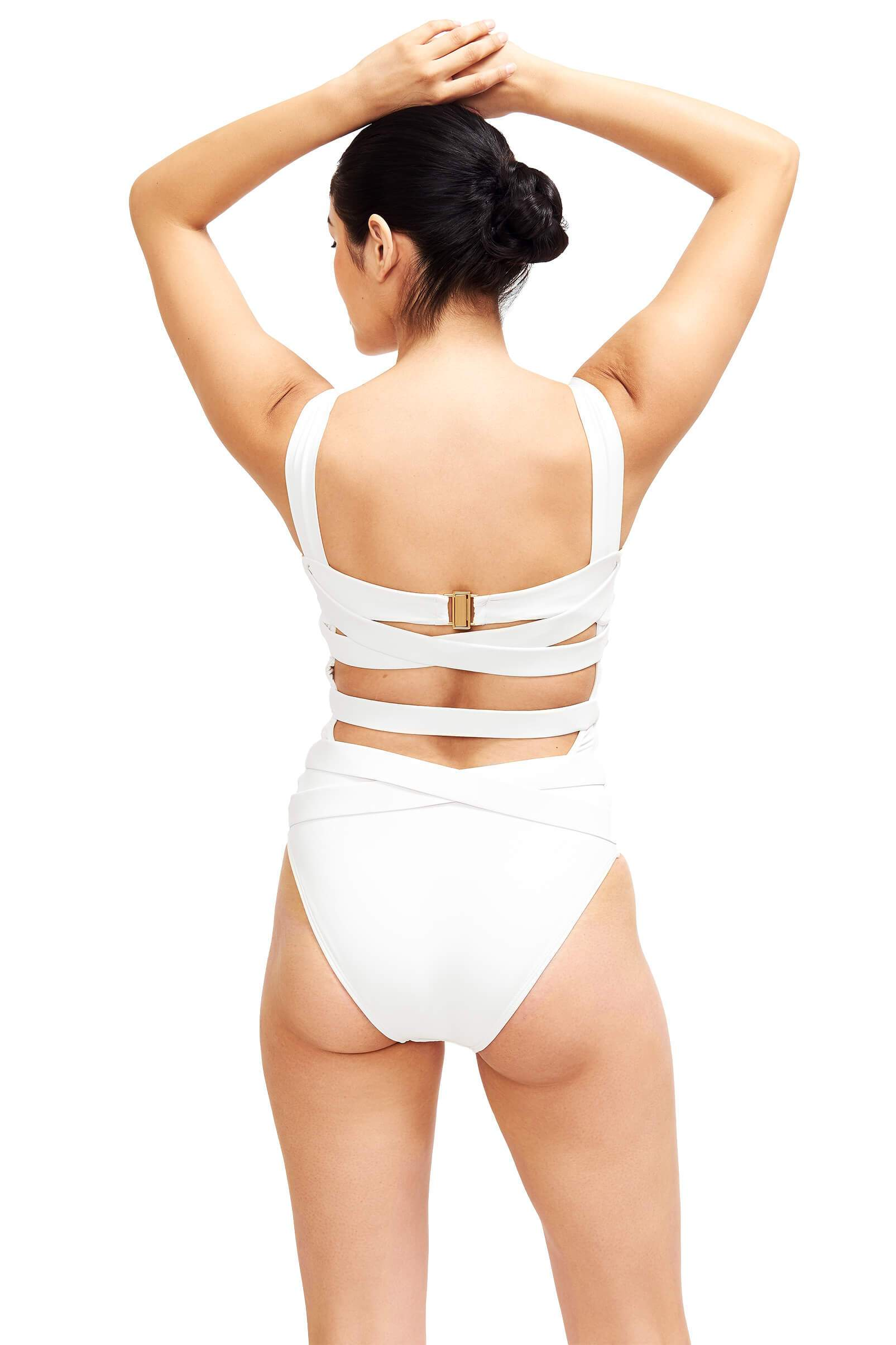 back of ivory one piece swim suit has thick strappy back and gold clasp closure