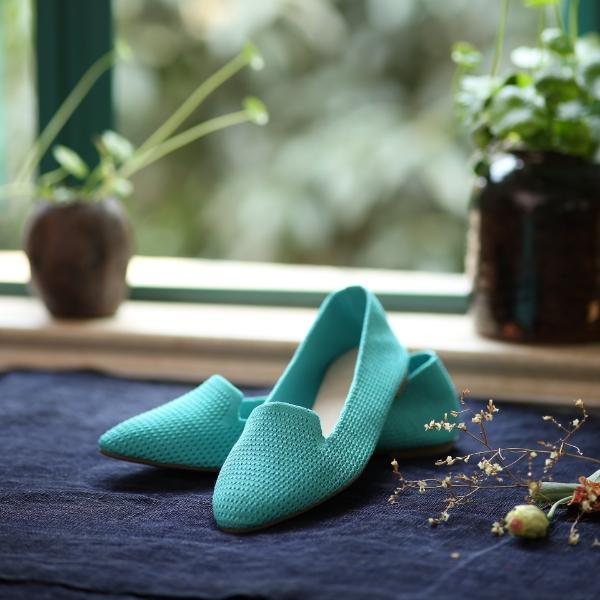 Blue knitted flats on top of one another with window and plants in the background