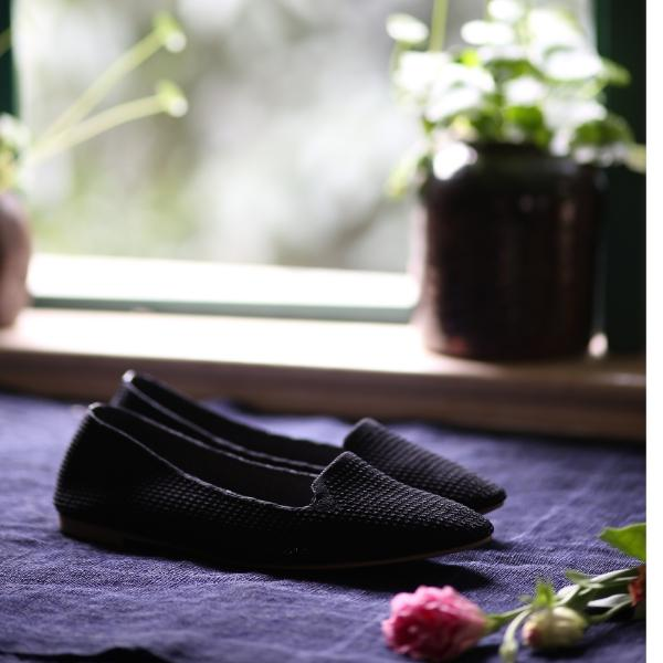 Black knitted slip on shoes with window and plants in the background