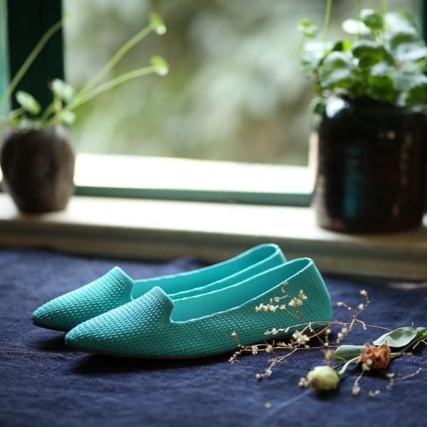 Blue knitted flat shoes near a window with plants in the background