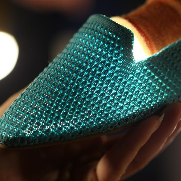 Close up of blue knitted flat slip on shoes