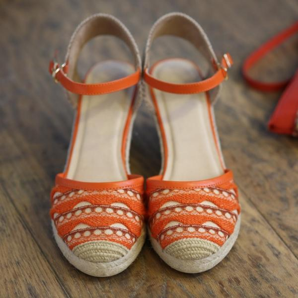 Close front view of wedge sandal with closed toe and orange woven detail