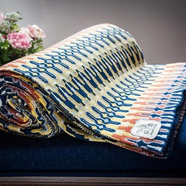 Close view of a rolled up throw blanket with yellow blue and orange pattern