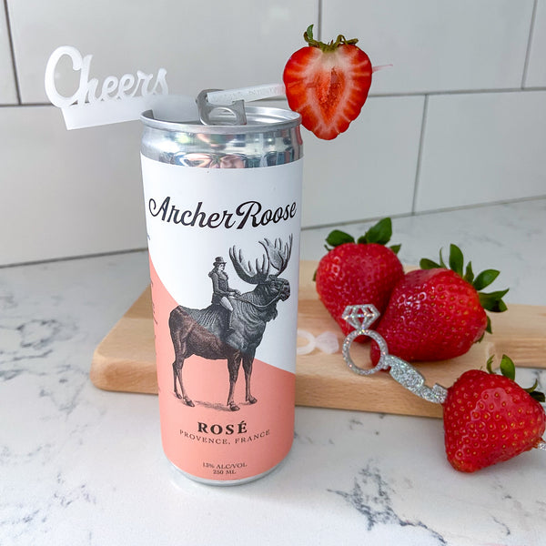 """Archer Roose Rose canned wine reviewed by The Pursuit of Cocktails styled with a """"cheers"""" Swizzly Stick"""