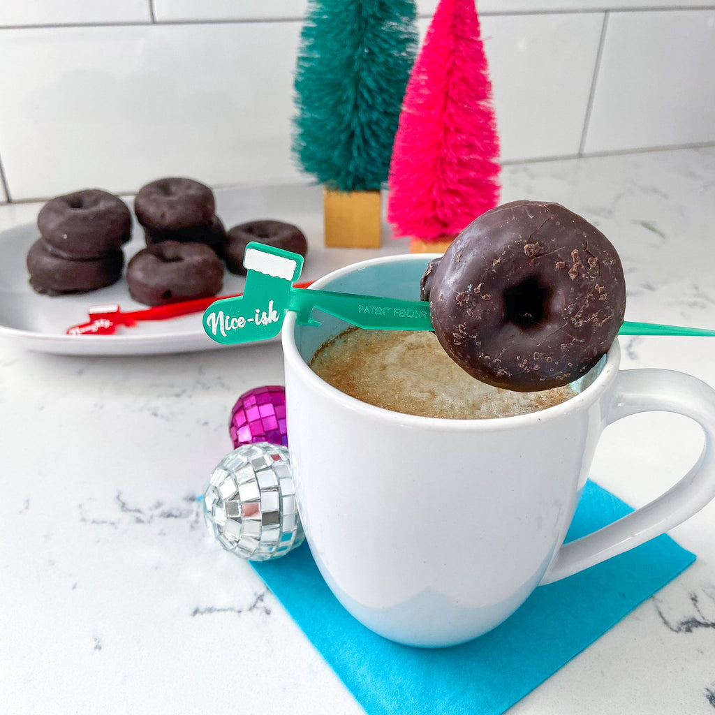 Santa's List themed cocktail pick Swizzly with mini donut garnish on a mug of coffee