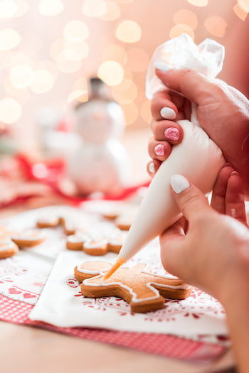 Our favorite traditional Christmas recipes. This is an image of someone putting icing onto gingerbread cookies.
