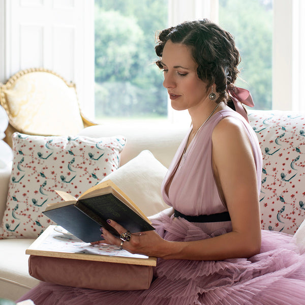Ellen Green reading a book, surrounded by G&H cushions with a bird pattern on. The dress she wears is pink and she is sitting on a sofa in front of a well lighted window that shows a garden