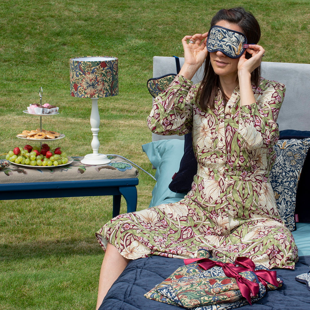 Ellen, G&H's Managing Director, is wearing a William Morris Navy and Indigo Eye mask, laying on a bed in a garden. There is a table next to her with a Golden Lily Lampshade and lamp stand.