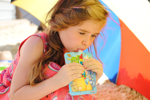girl eating from a yogurt pouch