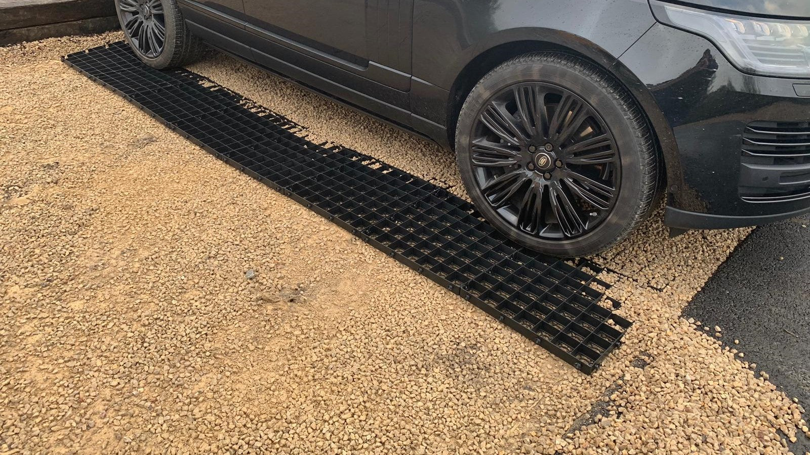 Gravel grid trays to reinforce a gravel driveway parking space