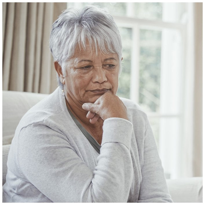 senior woman sitting on sofa thinking about how to talk to a loved one about incontinence