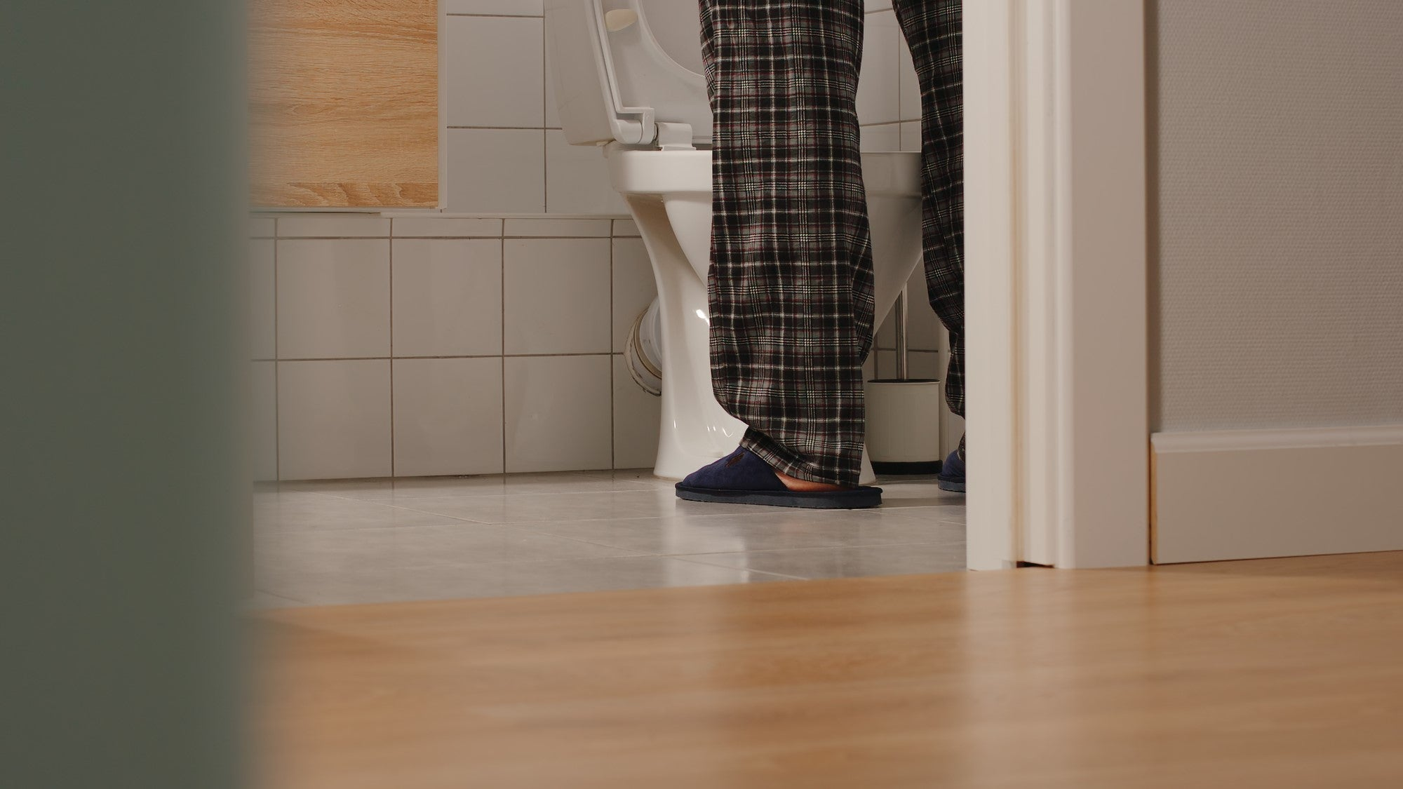 man in pyjamas and slippers standing at toilet, only lower legs visible