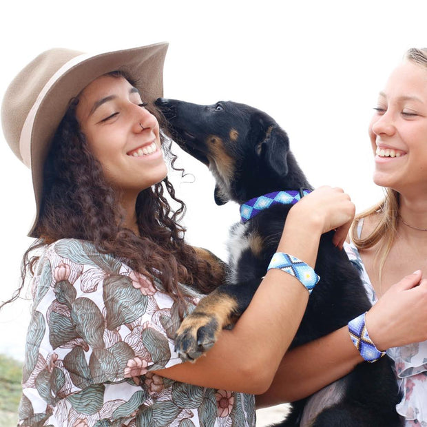Two girls holding dog wearing matching Aquata seed bead collar and bracelets