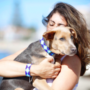 Woman holds dog outside wearing matching Aquata seed bead bracelet and dog collar