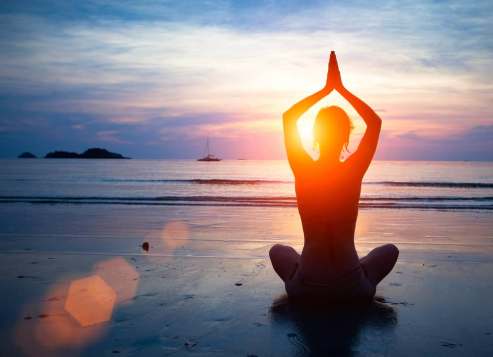 woman doing yoga on beach with new thought mind science focus