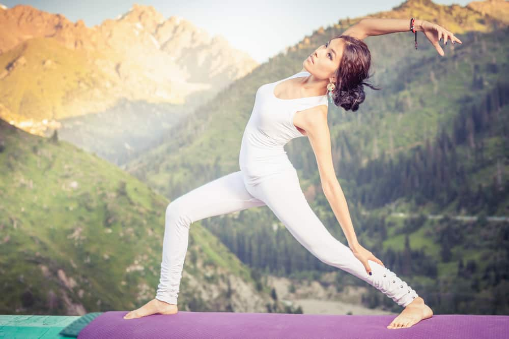 asian woman doing exercise of qigong at mountain range