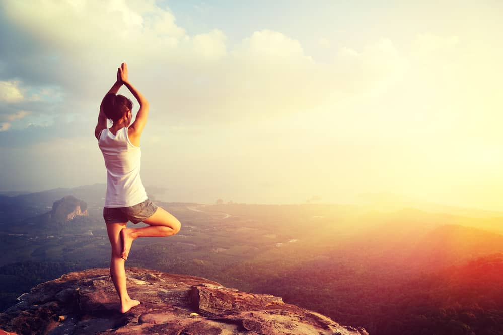 girl doing yoga on top of mountain