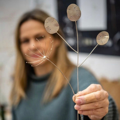 Silversmith Josephine Gomersall holding two of her Florilegium collection pieces