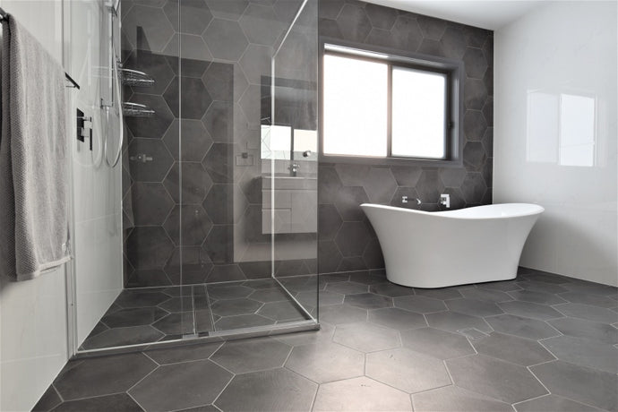 #84 - Bathrooms: Hexagonal charcoal tiles contrast against all-white walls and furniture