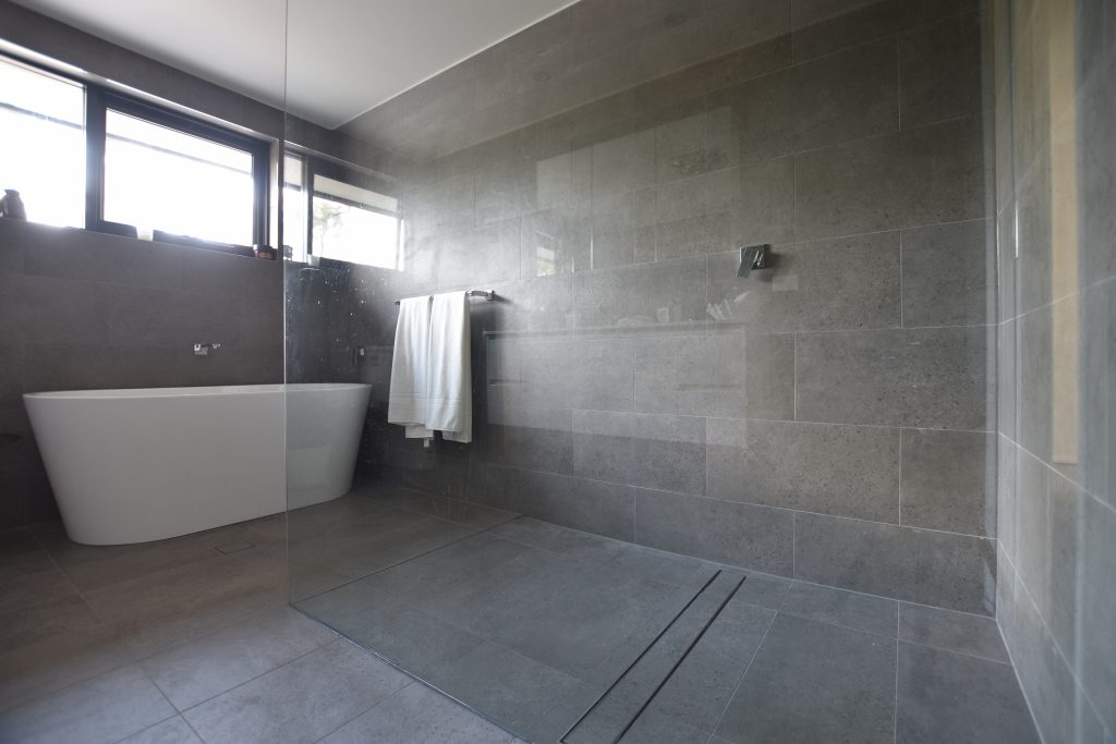 Bathroom with walk in shower and long tile insert grate, this is good for cleaning.